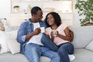 couple-sitting-on-couch-enjoying-their-home