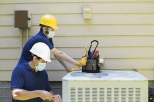 two-techs-working-on-outside-ac-unit