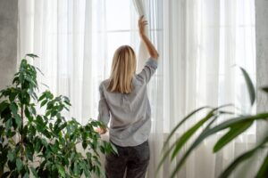 woman-adjusting-curtain-in-home
